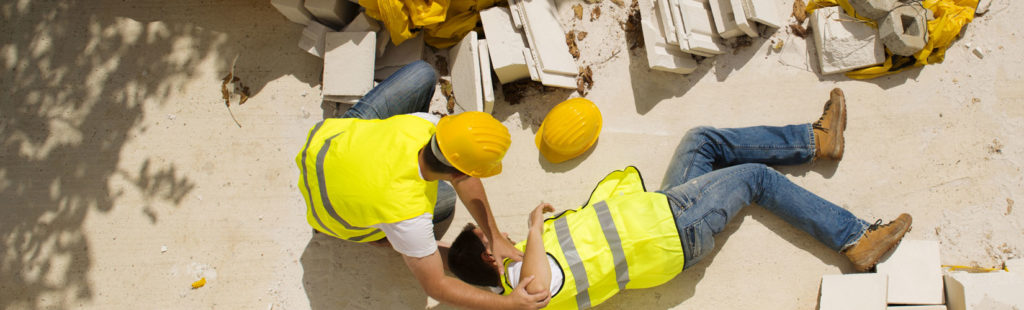 A construction worker lies on the ground after an injury as his colleagues rush to his side. An Arizona construction accident lawyer can get much needed compensation.