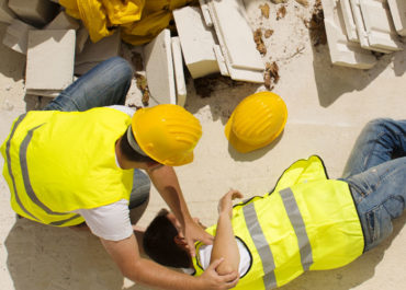 A construction worker lies on the ground after an injury as his colleagues rush to his side.