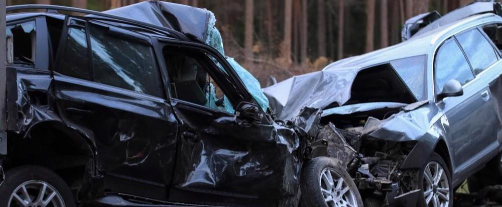 Two cars are shown totaled after a head-on collision.
