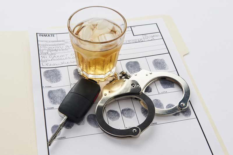 Drink, car keys and handcuffs on a police department desk