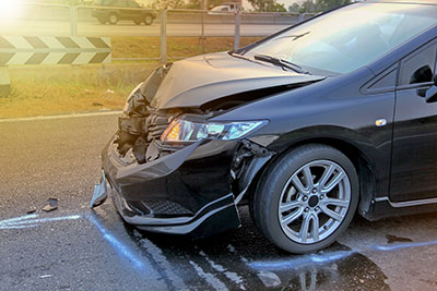 A damaged vehicle is shown on the side of a road after a hit-and-run accident.