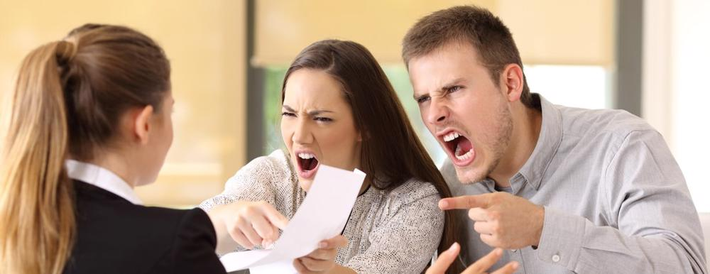 This image shows a couple angry at a bad faith insurance agent.