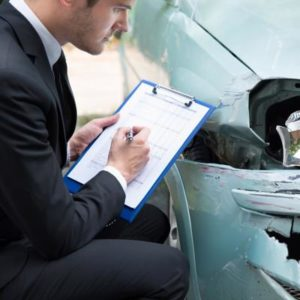 An insurance adjuster evaluates a vehicle after an Arizona car accident.