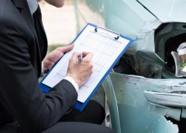 An insurance adjuster evaluates a vehicle after an Surprise car accident.