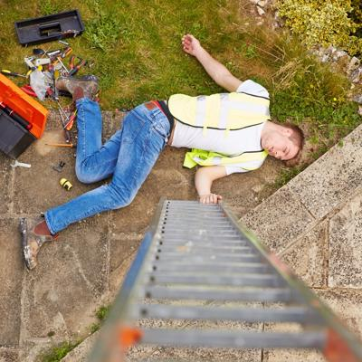 A construction worker lies unconscious on the ground after a work injury.