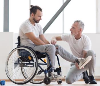 This image shows a therapist doing rehab with a paralyzed patient. An Arizona paralysis lawyer will seek compensation for a lifetime of care.