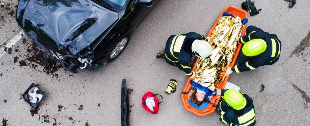 This image shows a woman on a stretcher after a defective seatbelt injury in a car accident.