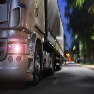 This image shows a semi-truck driving on the road at night.