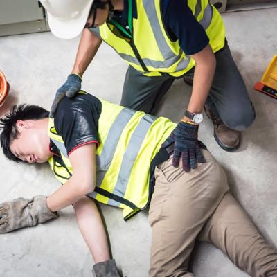 A man lies on the floor after a work injury as his co-worker attends to him.