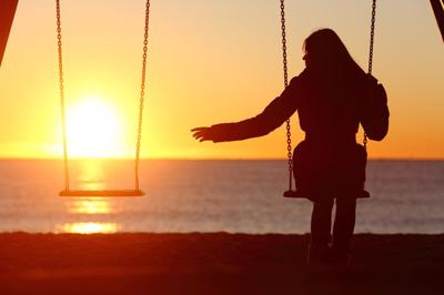 A woman sits on a swing over looking water as the sunsets, with an empty swing beside her.